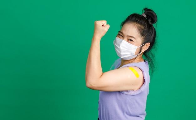 アジアの幸せで強い健康な中年の女性患者のスタジオショットは、コロナウイルスcovid 19ワクチンを受けた後、拳を上げてカメラを見て、筋肉と青い包帯石膏を見せてください。