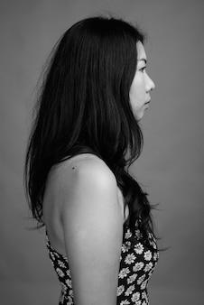 Студийный снимок азиатской женщины в платье на сером фоне в черно-белом