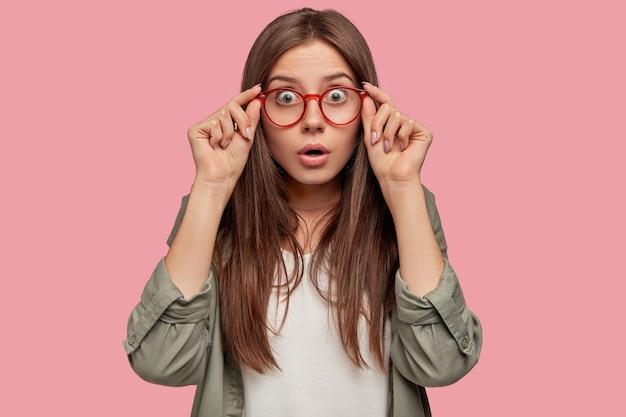Студийный снимок изумленного студента, позирующего на розовой стене