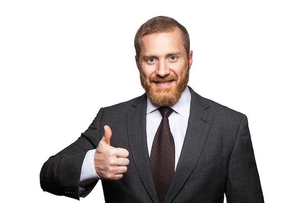 魅力的なビジネスマンのスタジオショット。親指を立てて、カメラを見て、白で隔離の幸せな実業家。