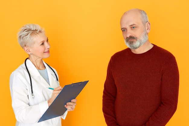 魅力的な自信を持って中年の女性医師がクリップボードを持って首に聴診器を持ち、悲しいusnhavenの年配の男性を治療しながら症状を手書きし、血液検査を注文するスタジオショット