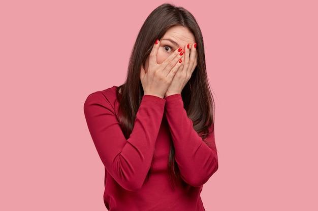 Студийный снимок привлекательной женщины смотрит сквозь пальцы, закрывает лицо руками, у нее красный маникюр, носит повседневную одежду, позирует на розовом фоне