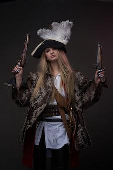 총과 어두운 배경에 트라이콘을 가진 매력적인 여성 해적의 스튜디오 샷.