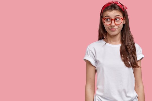 好奇心旺盛な表情で脇に集中した魅力的な若い女性のスタジオショット、長い髪
