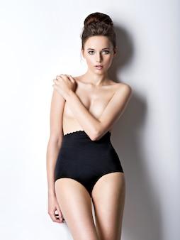 검은 란제리를 입고 아름답고 섹시한 젊은 여성의 스튜디오 샷