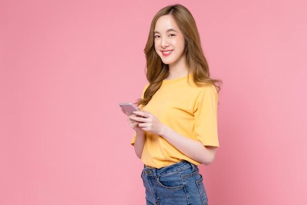 Студийный снимок красивой азиатской женщины, держащей смартфон и улыбающейся на светло-розовом фоне