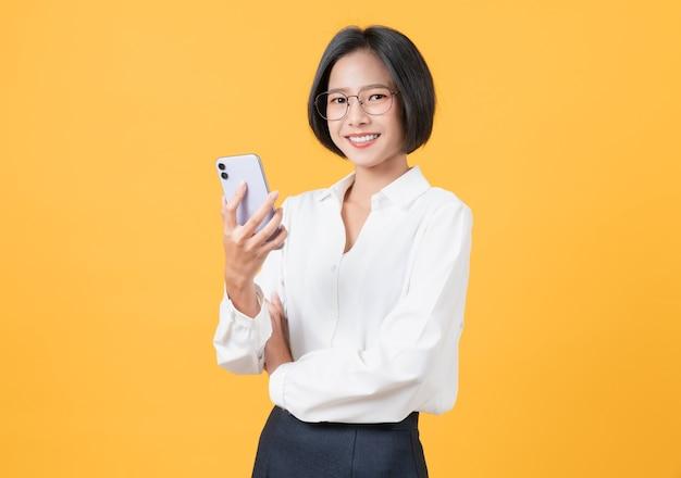 스마트폰을 들고 밝은 노란색 배경에 웃고 있는 아름다운 아시아 여성의 스튜디오 샷.
