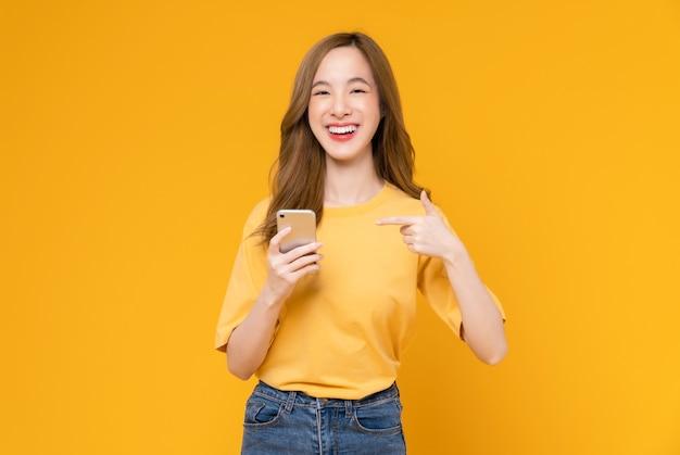 스마트폰을 들고 밝은 노란색 배경에서 웃고 있는 아름다운 아시아 여성의 스튜디오 샷