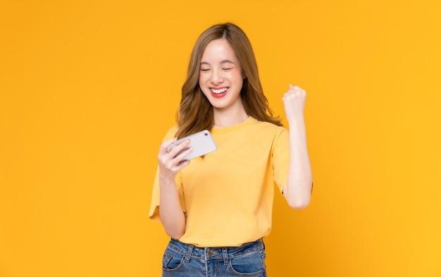 Студийный снимок красивой азиатской женщины, держащей смартфон и улыбающейся на светло-желтом фоне