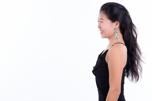 白い背景に対して隔離のパーティーの準備ができてノースリーブのドレスと美しいアジアの女性のスタジオショット