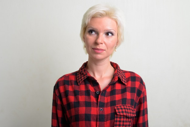 白い背景の短い髪の美しい金髪の流行に敏感な女性のスタジオショット