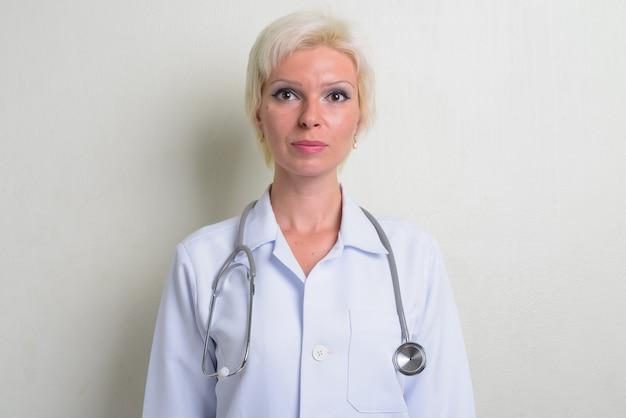 白い背景の短い髪の美しいブロンドの女性医師のスタジオショット