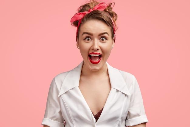 Студийный снимок красивой радостной женщины удивительно смотрит в камеру, широко открывает глаза и рот, удивляется, получив неожиданный подарок