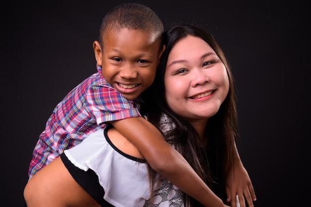 美しい太りすぎのアジアの女性と黒の背景に一緒に若い多民族のアジアの少年のスタジオ撮影