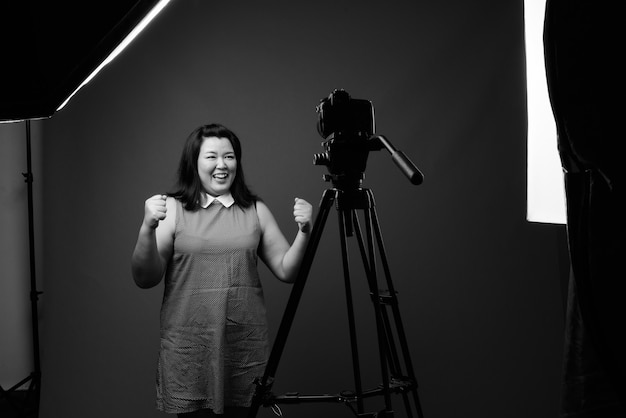 Студийный снимок красивой полной азиатской женщины в платье на сером фоне в черно-белом