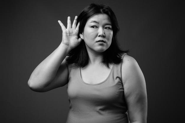 黒と白の灰色の背景にノースリーブのドレスを着ている美しい太りすぎのアジアの女性のスタジオショット