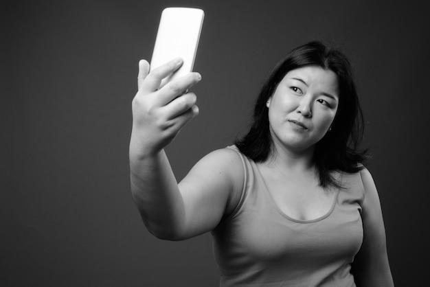 Студийный снимок красивой полной азиатской женщины в платье без рукавов на сером фоне в черно-белом