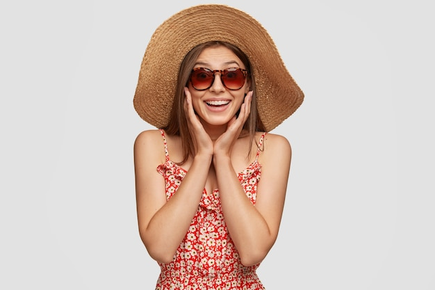 Студийный снимок красивой довольной туристки, которая проводит летние каникулы за границей, улыбается во время чудесной экскурсии, носит солнцезащитные очки.