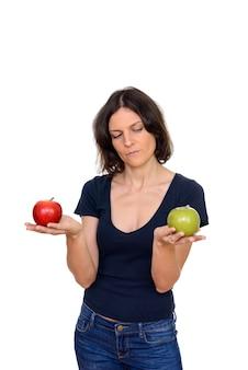 흰색 배경에 대해 격리 빨강 및 녹색 사과 사이 선택 아름다운 여자의 스튜디오 샷