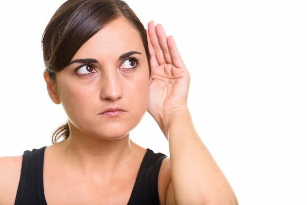 Студийный снимок красивой женщины, думающей и слушающей