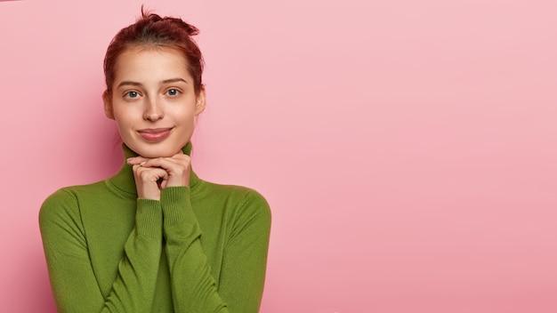 美しい若い白人女性のスタジオショットは、手のひらをあごの下に置き、穏やかな表情でカメラを見つめ、緑のタートルネックを身に着け、自然の美しさを持ち、ピンクの壁に隔離され、空白のスペースを脇に置きます