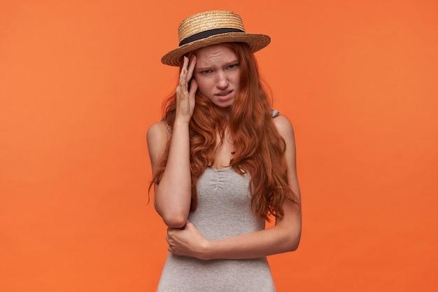 彼女の手のひらの後ろに隠れている波状のセクシーな髪を持つ美しい若い赤毛の女性のスタジオショット、恥ずかしい顔でカメラに有罪に見える、オレンジ色の背景の上に分離