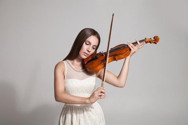 Студия выстрел брюнетка в белом платье играет на скрипке. белый фон