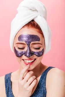 스파 치료 동안 웃 고 평온한 여자의 스튜디오 샷. 분홍색 배경에 포즈 얼굴 마스크와 감정적 인 여성 모델.