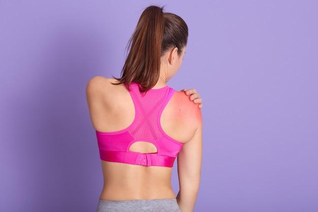 Съемка студии кавказской здоровой девушки имея боль в плече, задний взгляд спортивной женщины
