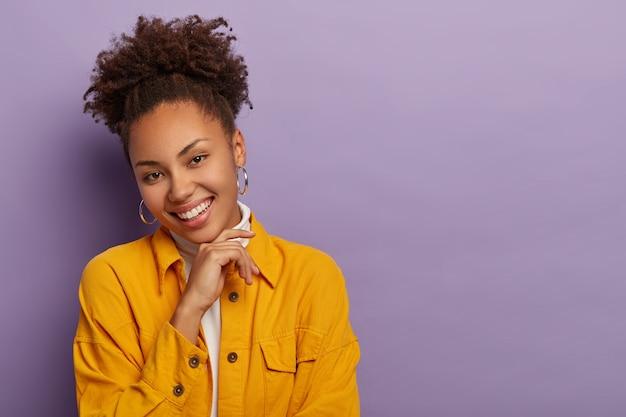 곱슬 빗질 된 조랑말 꼬리를 가진 매력적인 기쁘게 젊은 여성의 스튜디오 샷, 턱을 부드럽게 만지고 기꺼이 미소 짓고 세련된 노란색 재킷을 입고 둥근 큰 귀걸이
