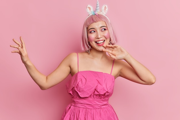쾌활한 아시아 여자의 스튜디오 샷은 경쾌한 분위기가 춤을 추며 평온한 팔을 입고 축제 드레스를 입고 밥 헤어 스타일을 가지고 있습니다.