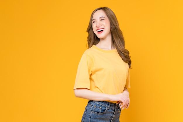 쾌활한 아름다운 아시아 여성이 티셔츠를 입고 노란색 배경에 서 있는 스튜디오 샷.