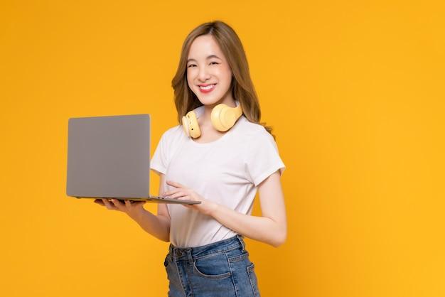 흰색 티셔츠를 입고 노란색 배경에 빈 화면의 노트북 모형을 들고 있는 쾌활한 아름다운 아시아 여성의 스튜디오 샷.