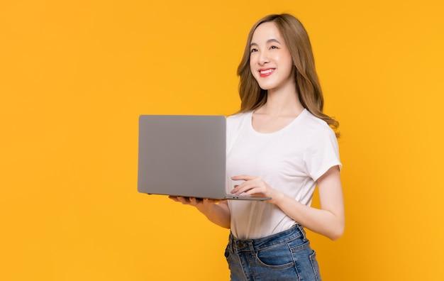 흰색 티셔츠를 입고 노란색 배경에 키보드로 타이핑한 노트북을 들고 있는 쾌활한 아름다운 아시아 여성의 스튜디오 샷.