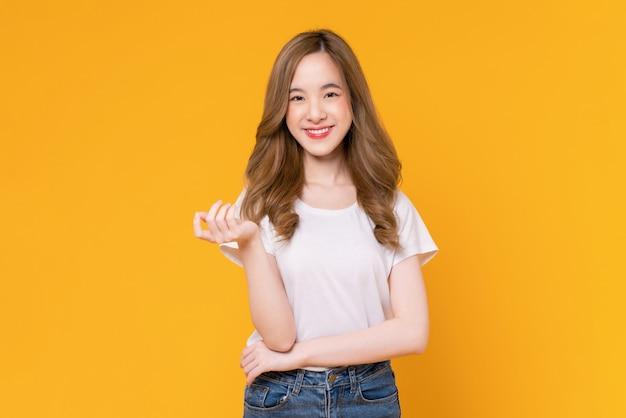 흰색 티셔츠를 입고 노란색 배경에 서 있는 밝고 아름다운 아시아 여성의 스튜디오 샷.
