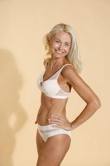 孤立して立っている間離れて微笑んでいるランジェリーの陽気な白人の成熟した女性のスタジオショット