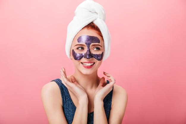얼굴 마스크와 쾌활 한 아가씨의 스튜디오 샷입니다. 분홍색 배경에 포즈 머리에 수건에 흥분된 소녀.