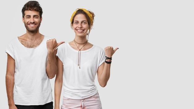 Студийный снимок веселых приятных на вид мужчины и дамы с зубастой улыбкой, показывает пальцем в сторону, показывает свободное место для вашей рекламы