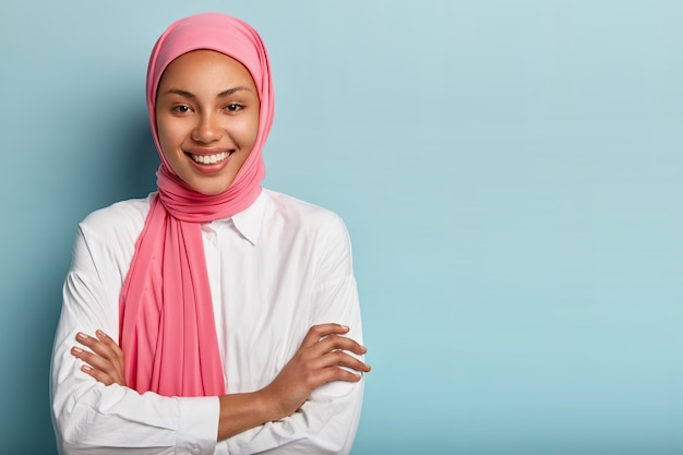 쾌활한 종교 무슬림 여성의 스튜디오 샷은 팔을 접고 넓게 미소 짓고 하얀 치아를 가지고 있습니다.