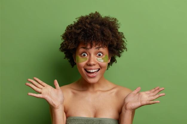 쾌활한 여자의 스튜디오 샷은 손바닥이 행복하게 반응하여 눈 아래 콜라겐 패치를 적용하여 붓기를 줄이고 녹색 스튜디오 벽 위에 고립 된 주름을 잡습니다.