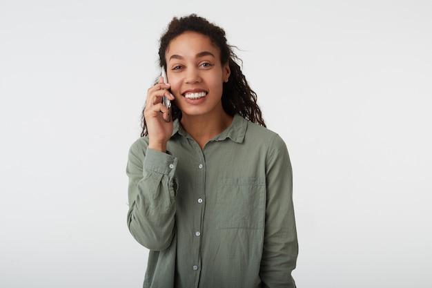 Студийный снимок веселой молодой милой темноволосой кудрявой темнокожей женщины, приятно улыбающейся во время телефонного разговора, стоящей на белом фоне в зеленой рубашке