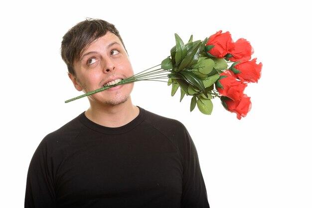 赤いバラを噛んで考えている狂気の白人男性のスタジオショット