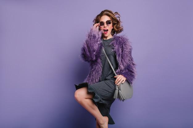 写真撮影中にジャンプする毛皮のコートを着た裸足の巻き毛の女の子のスタジオショット
