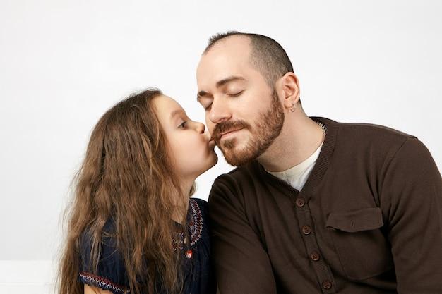 Студийный снимок милой очаровательной маленькой девочки с длинными пышными волосами, целующей своего небритого отца в щеку, показывая свою благодарность за подарок на день рождения