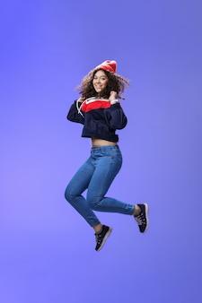 ふざけて気楽にジャンプするビーニースウェットシャツとスニーカーの巻き毛のかわいい女の子のスタジオショット...