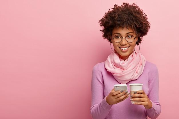 기뻐하는 아프리카 계 미국인 여성의 스튜디오 샷은 스마트 폰에서 인터넷을 서핑하고, 뉴스 피드를 확인하고, 종이컵에서 향기로운 커피를 마시고, 세련된 옷과 둥근 안경을 착용합니다.