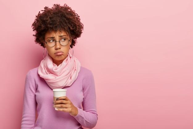 불쾌한 어두운 피부를 가진 여성의 스튜디오 샷은 아침 다과로 신선한 커피를 마신다.