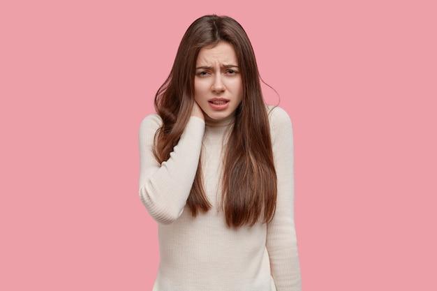 不機嫌なヨーロッパの女性のスタジオショットは、不満で顔を眉をひそめ、首に手を保ち、痛みから叫び、カジュアルなジャンパーを着て、ピンクのスタジオの壁にモデルを置きます。人