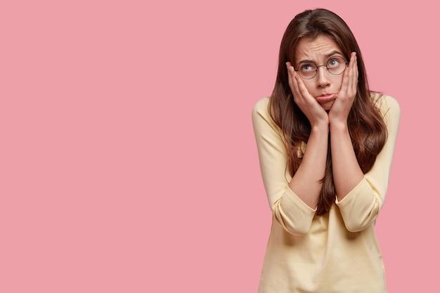 不機嫌な動揺した女性のスタジオショットは、カジュアルな黄色のセーターを着て、唇を財布に入れ、頬に手を保ちます