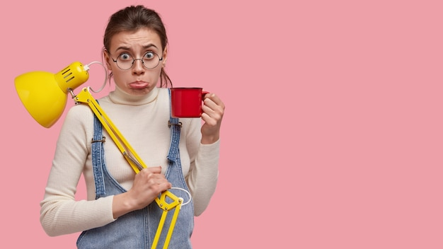 불쾌한 젊은 학생의 스튜디오 샷 아랫 입술 지갑, 커피 마시고 좋은 시력을 위해 책상 램프 사용